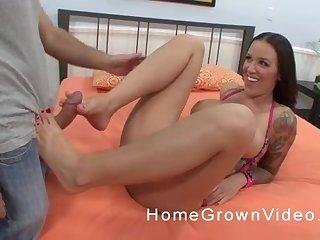 Tattooed busty brunette pornstar gets a cumshot all over her sexy feet