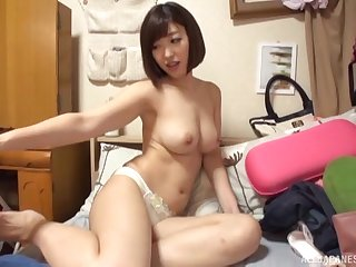 Busty short haired Japanese babe gives a titjob and rides cock